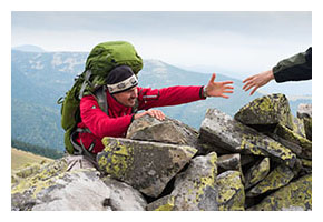 Backpacker reaching out his hand for help to climb over a rock